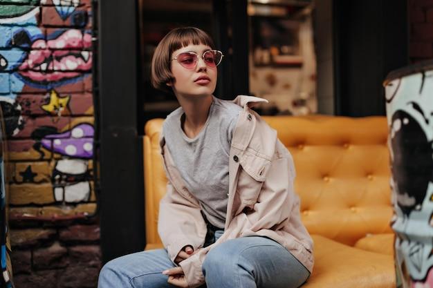 Stilvolle frau mit kurzen haaren posiert auf gelber couch im café