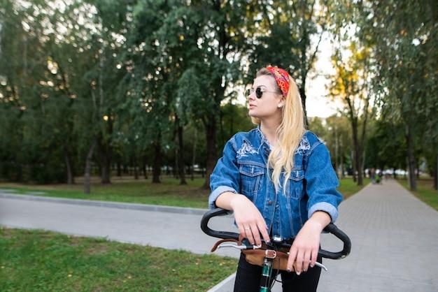 Stilvolle frau mit sonnenbrille und jeansjacke steht mit dem fahrrad im park und schaut zur seite.