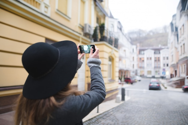 Stilvolle frau touristin macht ein foto der architektur. mädchen beschäftigt sich mit mobiler fotografie.