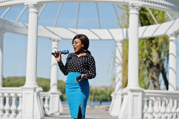 Stilvolle frau tv-moderatorin mit mikrofon in brille, blauem rock und schwarzer bluse im freien gegen weißen steinbogen mit handy gestellt