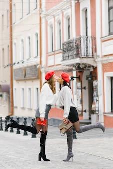 Stilvolle freundinnen in roten baskenmützen küssen sich gegenseitig auf die lippen