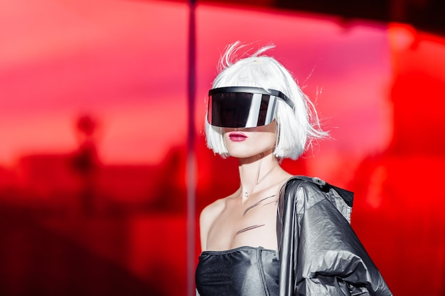 Stilvolle futuristische blondine im cyberpunk-stil auf einem roten spiegel.