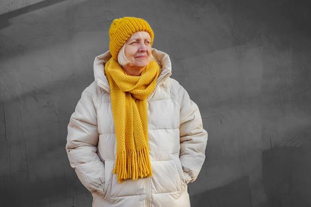 Stilvolle gealterte frau im warmen mantel mit gelbem strickschal und mütze