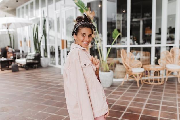 Stilvolle gebräunte frau im stirnband und in der rosa jeansjacke, die gegen straßencafé aufwirft