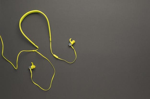 Stilvolle gelbe kopfhörer auf einem dunkelgrauen hintergrund. ausrüstung zum musikhören.