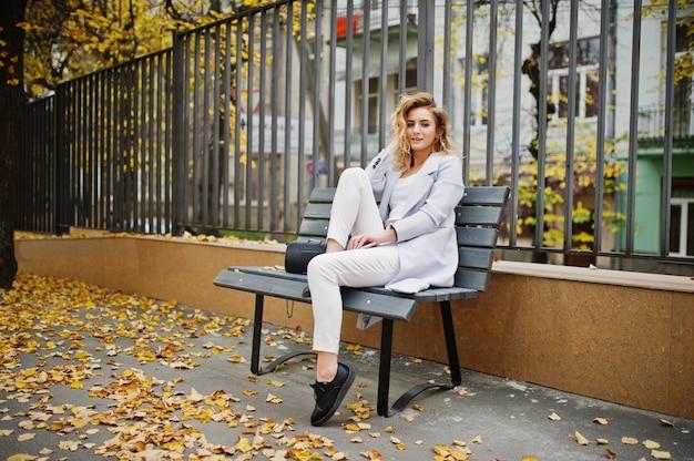 Stilvolle gelockte blonde vorbildliche mädchenabnutzung auf weiß mit tasse kaffee und handy auf den händen, die an der bank am fall aufwerfen.
