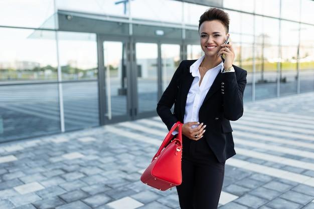 Stilvolle geschäftsfrau auf dem hintergrund eines modischen bürogebäudes