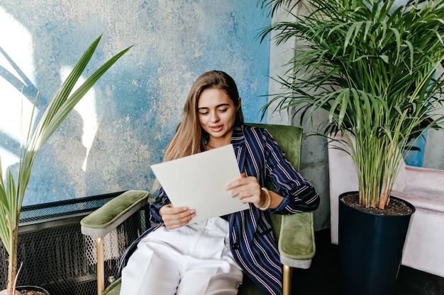 Stilvolle geschäftsfrau, die im büro mit zeitung aufwirft. attraktives kaukasisches mädchen, das dokumente liest.