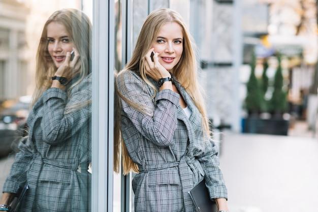 Stilvolle geschäftsfrau mit dem klemmbrett, das telefonanruf macht
