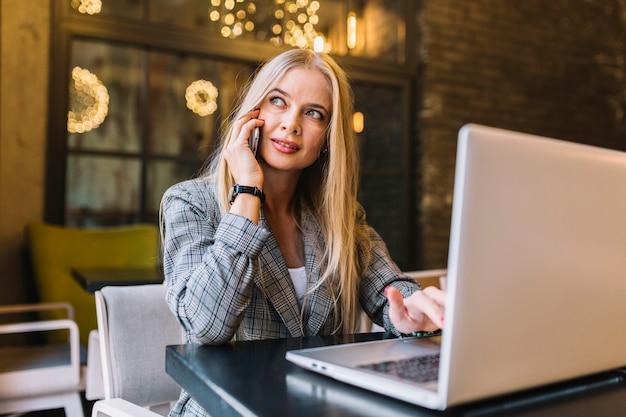 Stilvolle geschäftsfrau mit laptop am schreibtisch