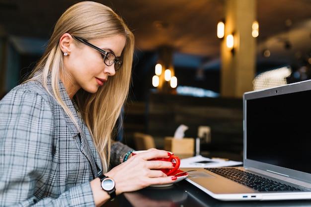 Stilvolle geschäftsfrau mit laptop in der gemütlichen kaffeestube