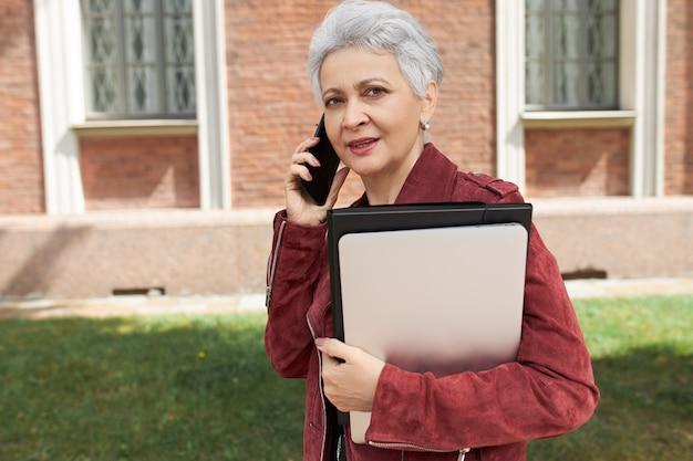 Stilvolle geschäftsfrau mittleren alters, die handy benutzt, um taxi zu rufen