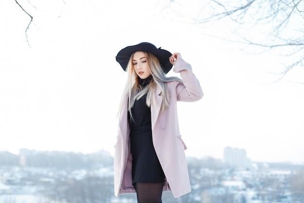 Stilvolle glamouröse elegante junge frau in einem rosa mantel in einem schwarzen hut in einem gestrickten kleid, das gegen einen weißen winterhimmel aufwirft. charmantes mädchen geht an einem wintertag.