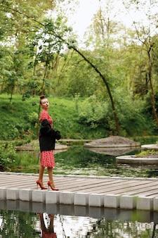 Stilvolle glamouröse kleidung für spaziergänge durch die stadt. modelspaziergänge im stadtpark am abend in rotem kleid und jacke.