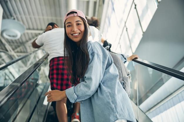 Stilvolle glückliche asiatin mit ihren freunden, die mit dem flugzeug in den urlaub reisen