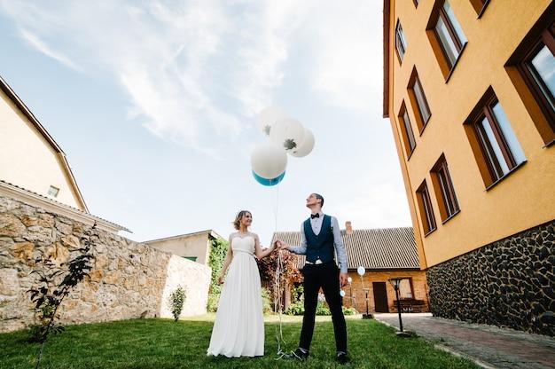 Stilvolle glückliche braut und bräutigam halten luftballons in den händen.