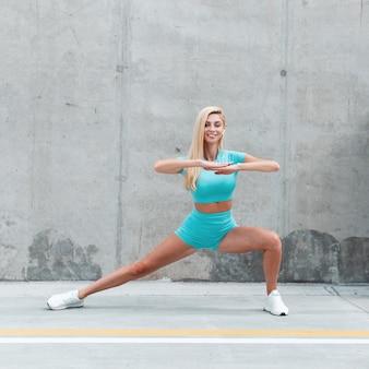Stilvolle, glückliche fitness-model-frau mit drahtlosem kopfhörer in modischer blauer sportbekleidung mit weißen schuhen, die sich strecken und auf der straße in der nähe der betonmauer trainieren