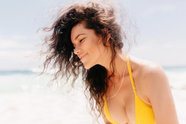 Stilvolle glückliche frau, die gelben badeanzug trägt, der auf der insel aufwirft