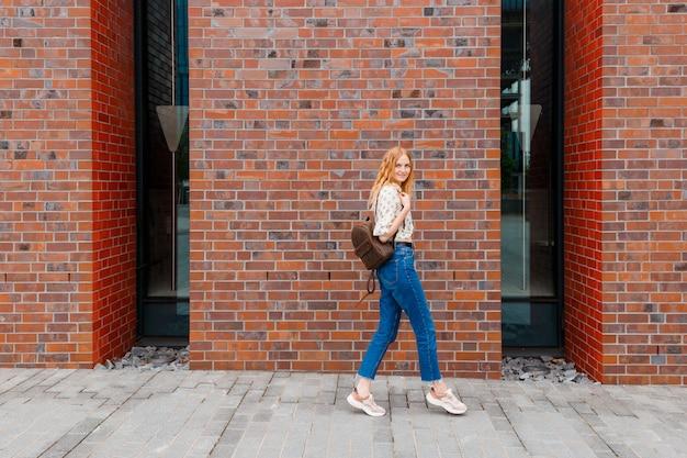 Stilvolle glückliche junge frau mit den blonden haaren, die an der stadtstraße aufwerfen