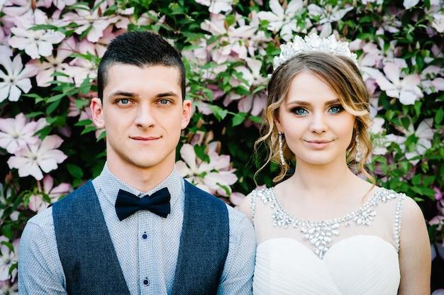 Stilvolle glückliche porträtbraut mit einer krone und einem bräutigam.