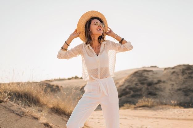 Stilvolle glückliche schöne lächelnde frau, die im wüstensand im weißen outfit mit strohhut und sonnenbrille auf sonnenuntergang aufwirft