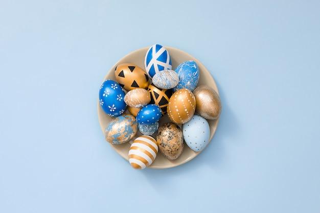 Stilvolle goldene dekorierte ostereier auf grauer platte lokalisiert auf blauer oberfläche. trendy flach lag ostern.