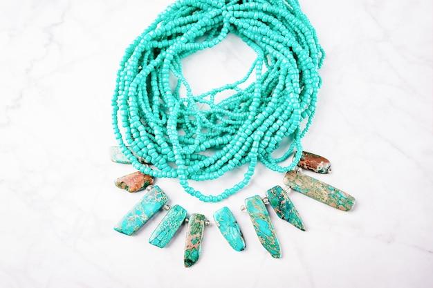 Stilvolle grüne türkisfarbene halskette auf weißem marmorhintergrund