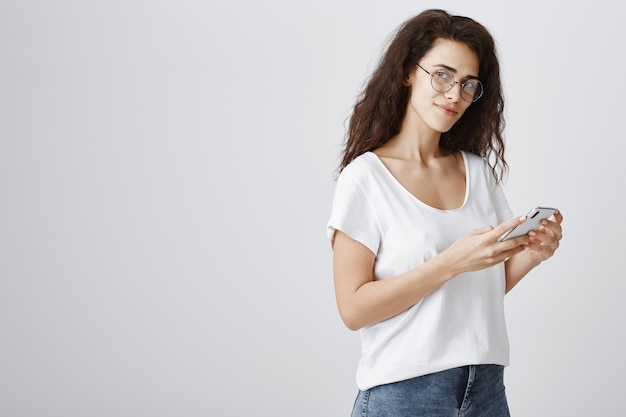 Stilvolle gutaussehende frau in brille mit handy