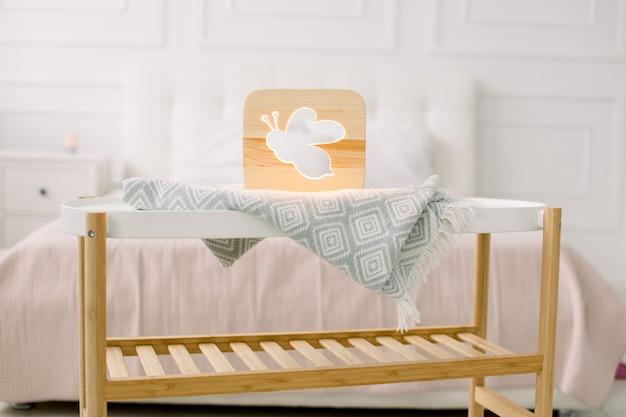 Stilvolle handgemachte holzlampe mit ausgeschnittenem bienenbild auf kleinem couchtisch, stehend im hellen hauptschlafzimmer.