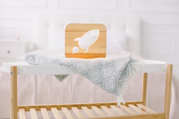 Stilvolle handgemachte holzlampe mit raketenausschnittbild, auf kleinem couchtisch, stehend im hellen hauptschlafzimmer.