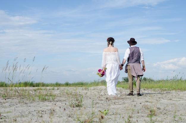 Stilvolle hippiefrau im weißen ethnischen kleiderhändchenhalten mit mann