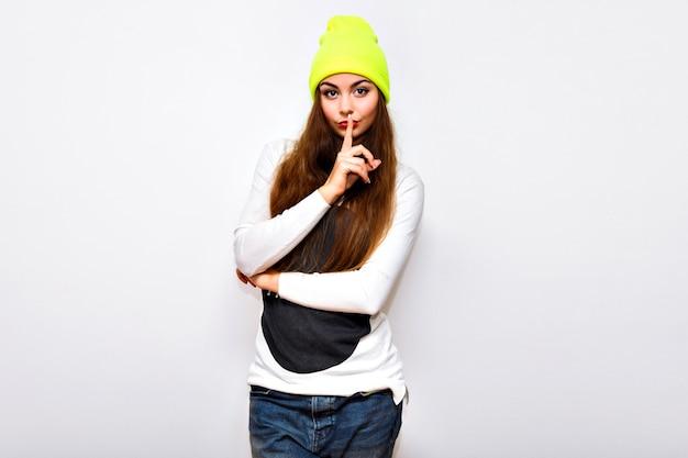 Stilvolle hipster-frau posiert gegen weiße wand, winterzeit, pullover, neonhut und jeans, lässiges trendiges sportliches outfit, lange haare, helles make-up, blitz, ernstes sexy gesicht.