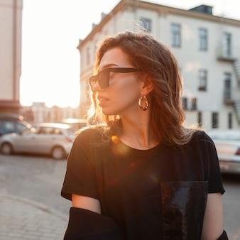 Stilvolle hübsche attraktive junge hipsterfrau in der trendigen dunklen sonnenbrille in einem stilvollen schwarzen t-shirt, das in der stadt bei sonnenuntergang aufwirft.