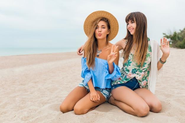 Stilvolle hübsche frauen sitzen auf sand in den sommerferien am tropischen strand, böhmischer stil, freunde reisen zusammen, modetrendzubehör, lächelnde glückliche emotion, positive stimmung, strohhut