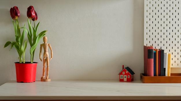Stilvolle inneneinrichtung mit tulpenblumentopf, büchern, dekorationen und kopierraum auf dem tisch