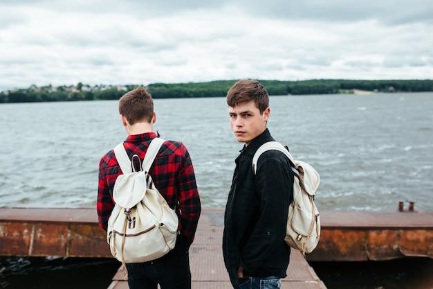 Stilvolle jugendliche mit rucksäcken aufwirft