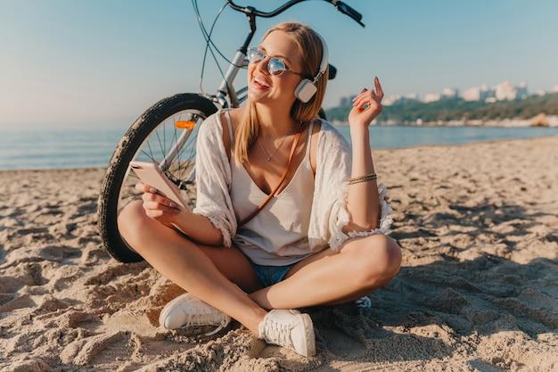 Stilvolle junge attraktive blonde lächelnde frau, die am strand mit dem fahrrad in den kopfhörern sitzt, die musik hören