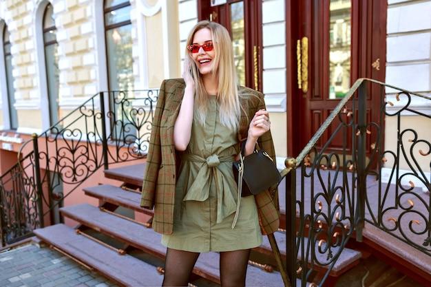 Stilvolle junge blonde geschäftsfrau, die durch ihr telefon spricht und auf der straße in paris posiert, trendiges stilvolles weibliches gutshof-outfit, übergroße jacke, warme farben.