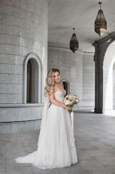 Stilvolle junge braut im klassischen hochzeitskleid posiert mit einem brautstrauß im freien weibliches modell in...