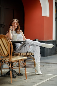 Stilvolle junge brünette schönheit, die leckere erfrischungen im straßencafé hat.