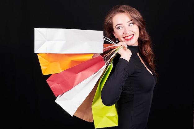Stilvolle junge brunettefrau, die bunte einkaufstaschen hält