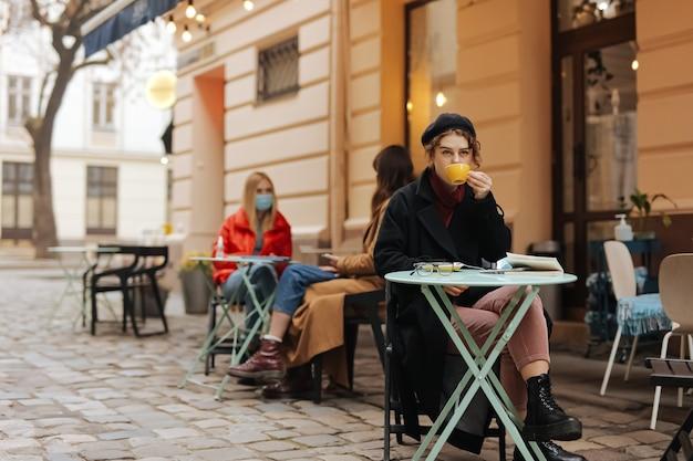 Stilvolle junge dame, die allein auf offener caféterrasse sitzt und frischen kaffee trinkt.