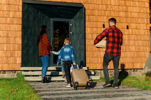 Stilvolle junge familie von eltern und zwei kindern, die gepäck vom auto zum haus tragen, das nach den ferien zurückkehrt.