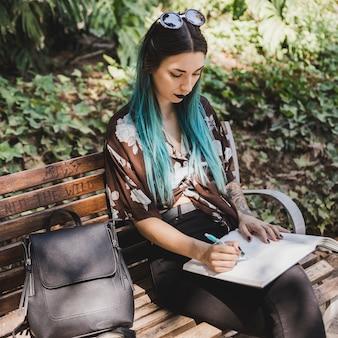 Stilvolle junge frau, die auf bankschreiben auf notizbuch mit stift sitzt