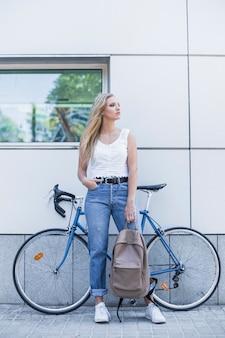 Stilvolle junge frau, die den rucksack steht gegen fahrrad hält