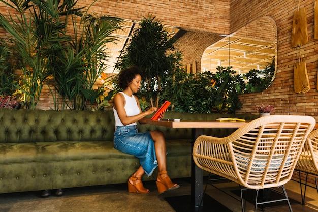 Stilvolle junge frau, die digitale tablette am restauranttisch verwendet