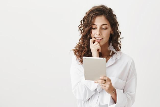 Stilvolle junge frau, die digitales tablett betrachtet und online einkauft