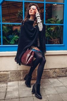 Stilvolle junge frau, die draußen gegen blaues fenster aufwirft. modisches outfit. schönes modell mit dem lockigen haarlächeln