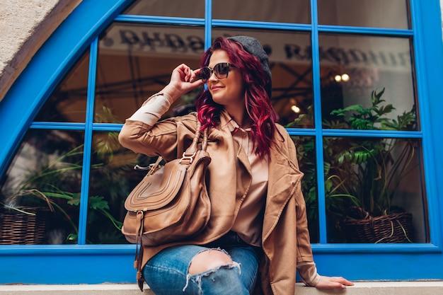 Stilvolle junge frau, die draußen gegen blaues fenster aufwirft. modisches outfit. schönes modell mit roten haaren lächelnd