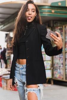 Stilvolle junge frau, die heraus ihre zunge beim nehmen von selfie am handy haftet